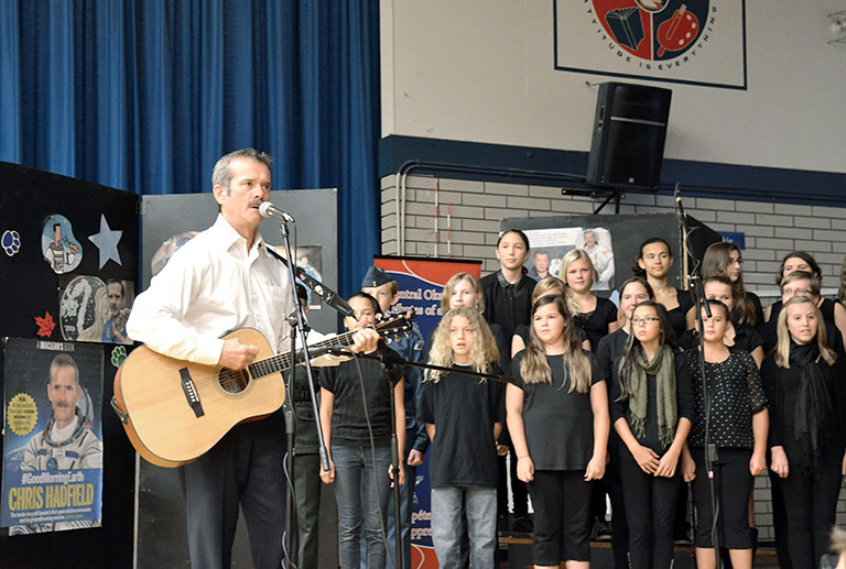 Col. Chris Hadfield plays the song, Is Somebody Singing, with students at École KLO Middle School. Photo credit: Paul Marck