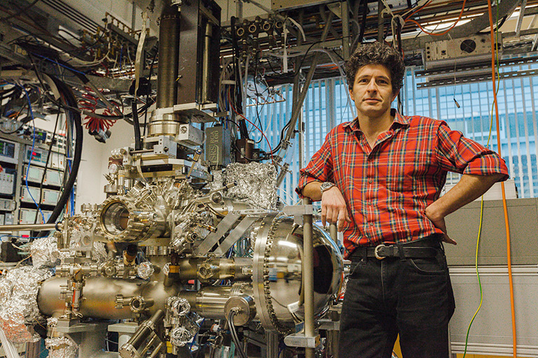Dr. Damascelli stands beside the experimental apparatus used to test his superconductivity theories. Photo credit: Hogan Wong