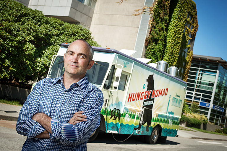 John Butt stands outside of the first food truck on campus, The Hungry Nomad. Photo credit: Martin Dee