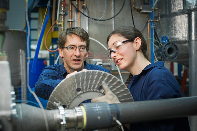 James Olson and Nici Darychuk examine a refiner plate to be used in a pilot scale experimental trial. Photo credit: Martin Dee